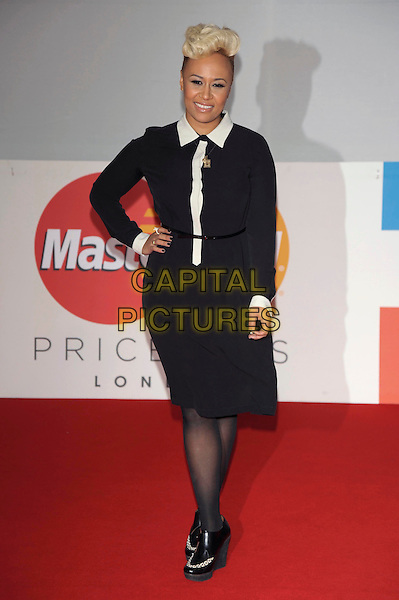 Emeli Sande.The Brit Awards 2012 arrivals, O2  Greenwich,  London, England 21st February 2012 .Brits full length black white dress belt hand on hip.CAP/PL.©Phil Loftus/Capital Pictures.