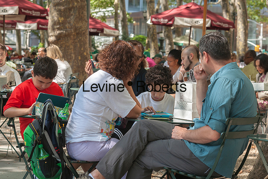 Visitors to Bryant Park in New York use their tablet computers on Thursday, August 15, 2013.  (© Richard B. Levine)