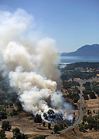 aerial photograph of a spreading grassfire near Lakeport, CA shortly after ignition, Clear Lake and Mount Konocti in the background, Lake County, California.