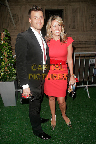 """GUEST & CLAIRE SWEENEY.attending the Cirque Du Soleil """"Varekai"""" Premiere at the Royal Albert Hall, London, England, January 8th 2007..full length red Roland Mouret Moon shift dress belt  funny gold clutch bag shoes  Clare.CAP/AH.©Adam Houghton/Capital Pictures."""
