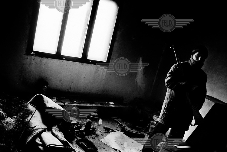 KLA fighter in a destroyed house in Studencane, Kosovo.