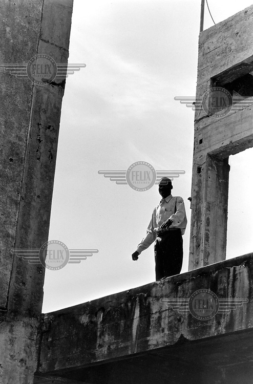 ©Crispin Hughes/Panos Pictures..Angola, Kuito. A teacher stands on the roof of the heavly shelled High School. In 1992, the civil war came to Kuito. A Unita offensive reached the centre of the town. The main street became a front line. The two sides blazed away at point-blank range. A ward of the hospital was bombed. The cathedral was destroyed. Almost every building in the city shows signs of damage. Stray shells killed and mained people in the barros. The dead were buried in unmarked graves in the park.