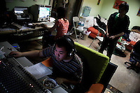 Jobby, Ruan Ruan, and Duwei (clockwise from bottom), guitarist, singer, and drummer for Chinese punk band Overdose, work and play computer games in Duwei's music studio in Nanjing, China.