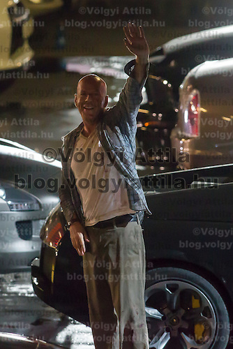 US actor Bruce Willis (R) waves to viewers surrounding the shooting of his next movie fifth in the Die Hard series titled Good Day to Die Hard in Budapest, Hungary on July 11, 2012. ATTILA VOLGYI
