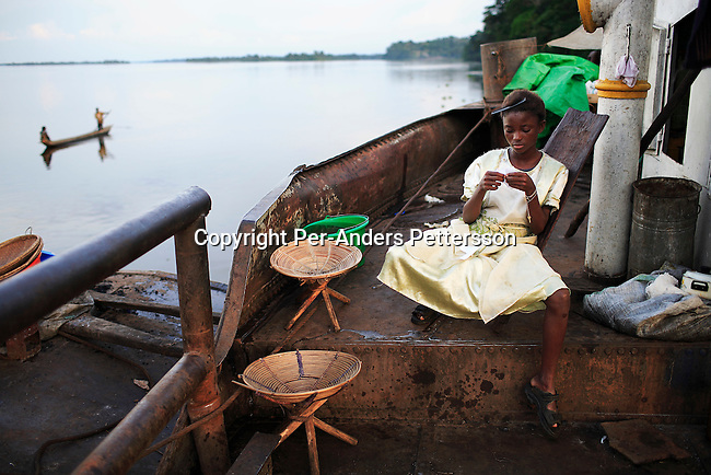LUKUTU, DEMOCRATIC REPUBLIC OF CONGO MARCH 15: Clarisse Mondo, age 13, waits for a boat to leave on March 15, 2006 in Lukutu, Congo, DRC. Clarisse traveled from Kisangani by herself as her sister died and she?s now going to look for her mother in Bumba, a journey of about a week. She haven?t seen her for ten years and don?t know her address. About five hundred people traveled on the boat from Kisangani to Kinshasa, a journey of about 1750 kilometers. It takes from 3-7 weeks, depending on the boat. Congo River is a lifeline for millions of people, who depend on it for transport and trade. During the Mobuto era, big boats run by the state company ONATRA dominated the traffic on the river. These boats had cabins and restaurants etc. All the boats are now private and are mainly barges that transport goods. The crews sell tickets to passengers who travel in very bad conditions, mixing passengers with animals, goods and only about two toilets for five hundred passengers. The conditions on the boats often resemble conditions in a refugee camp. Congo is planning to hold general elections by July 2006, the first democratic elections in forty years..(Photo by Per-Anders Pettersson/Getty Images)..