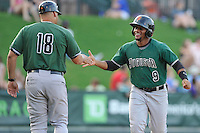 Designated hitter Miguel Gomez (9) of the Augusta GreenJackets is congratulated by manager Nestor Rojas (18) after scoring on a home run in a game against the Greenville Drive on Thursday, June 9, 2016, at Fluor Field at the West End in Greenville, South Carolina. Augusta won, 8-2. (Tom Priddy/Four Seam Images)