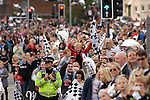 Fans watching Swansea City Football Club players and staff celebrating their promotion to the Premier League with an opentop bus tour of the city, where thousands of supporters turned out to show their appreciation..