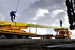 BARENDRECHT - Langs de snelweg A15 heeft BAM Grondtechniek de langste prefab-funderingspalen van Nederland geleverd voor de bouw van één van de hoogste geluidsschermen van Nederland. Het dertien meter hoge en twee kilometer lange scherm is door BAM Wegen Regio West in samenwerking met Redubel (onderdeel van BAM Wegen) ontwikkeld en gebouwd. Het scherm komt te rusten op 600 prefab-palen, waarvan acht palen een recordlengte van 39 meter hebben. De 20 ton zware palen zijn gemaakt door Lodewikus Voorgespannen Beton in Oosterhout, en worden door een Hitachi 300 GLS van BAM Grondtechniek de grond ingeslagen. Als verwijzing naar de nautische activiteiten van de havenstad, zijn de vlakverdelingen van de wand, net zo groot als die van zeecontainers. COPYRIGHT TON BORSBOOM