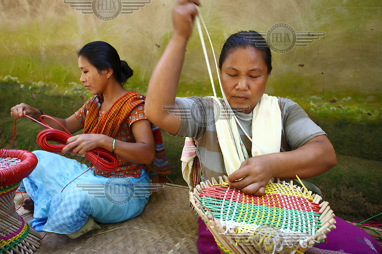Two Garo women weave colourful baskets. The Garo (or Mandi, as they refer to themselves) are an ethnic minority thought to be of Tibeto-Burmese origin. Prior to British rule they were mostly anamists but missionary work led the majority to convert to Christianity. The Garo of the Madhupur forest have long been under the threat of eviction by the government and the forest that they gain much of their livelihood from is being rapidly destroyed by unregulated logging.