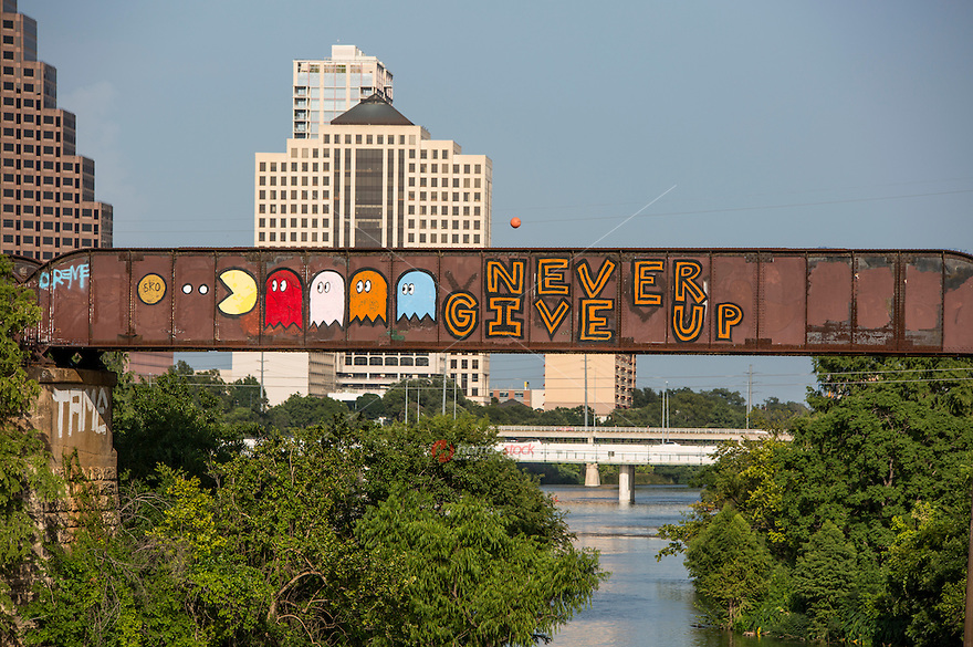"Creative graffiti artist paint colorful and inspiring messages such as the ""Never Give Up"" graffiti mural painting on the Austin Railroad Graffiti Bridge over Lady Bird Town Lake, Austin, Texas."
