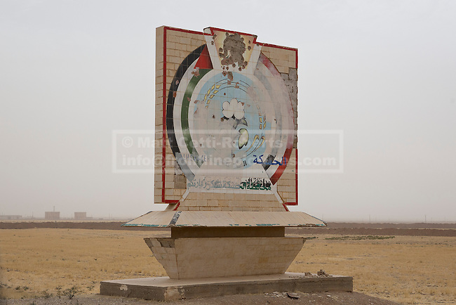 28/09/2014. Al-Yarubiyah, Syria. Pock marked by bullets, a sign thanking people for visiting Syria's Hasakah Governate is seen on the outskirts of the Syrian border town of Al-Yarubiyah.<br /> <br /> Facing each other across the Iraq-Syria border, the towns of Al-Yarubiyah, Syria, and Rabia, Iraq, were taken by Islamic State insurgents in August 2014. Since then The town of Al-Yarubiyah and parts of Rabia have been re-taken by fighters from the Syrian Kurdish YPG. At present the situation in the towns is static, but with large exchanges of sniper and heavy machine gun fire as well as mortars and rocket propelled grenades, recently occasional close quarter fighting has taken place as either side tests the defences of the other.