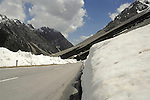 Empty road through the mountains with snow piled to the side. St Anton district, Tyrol, Tirol, Austria.