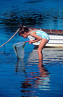 Young girl in bathing suit wading with a fishing net in the water and hoping to catch some minnows.