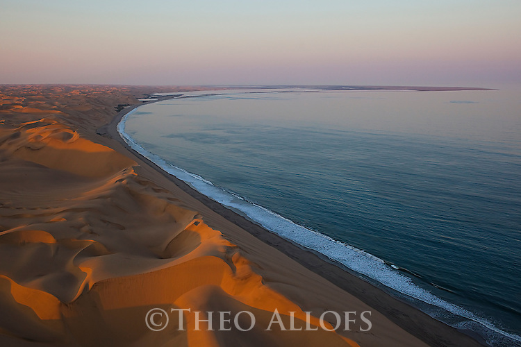 Namibia;  Namib Desert, Skeleton Coast, red sand dunes and Pacific Ocean south of Walvis Bay, aerial view