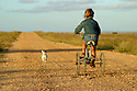 Young girl riding bike down a dusty road. Australia.