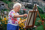 elderly woman painting landscape in garden