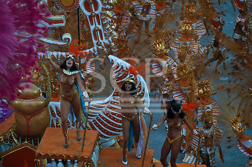 Rio de Janeiro, Brazil. Samba dancers in very brief gold bikini costumes during the carnival parade on a float in the Sambadrome.
