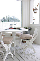 An outdoor dining area is sheltered from the snow by the clapboard walls of a partly enclosed veranda