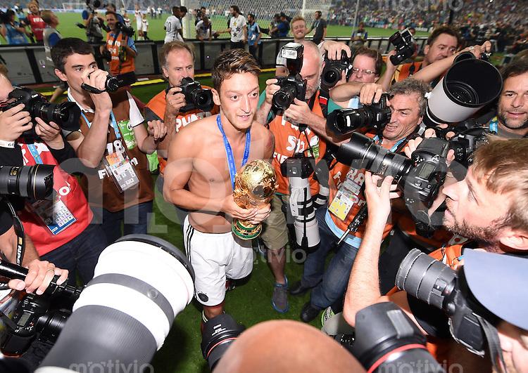 FUSSBALL WM 2014                       FINALE   Deutschland - Argentinien     13.07.2014 DEUTSCHLAND FEIERT DEN WM TITEL: Mesut Oezil jubelt mit dem WM Pokal, umringt von Fotografen