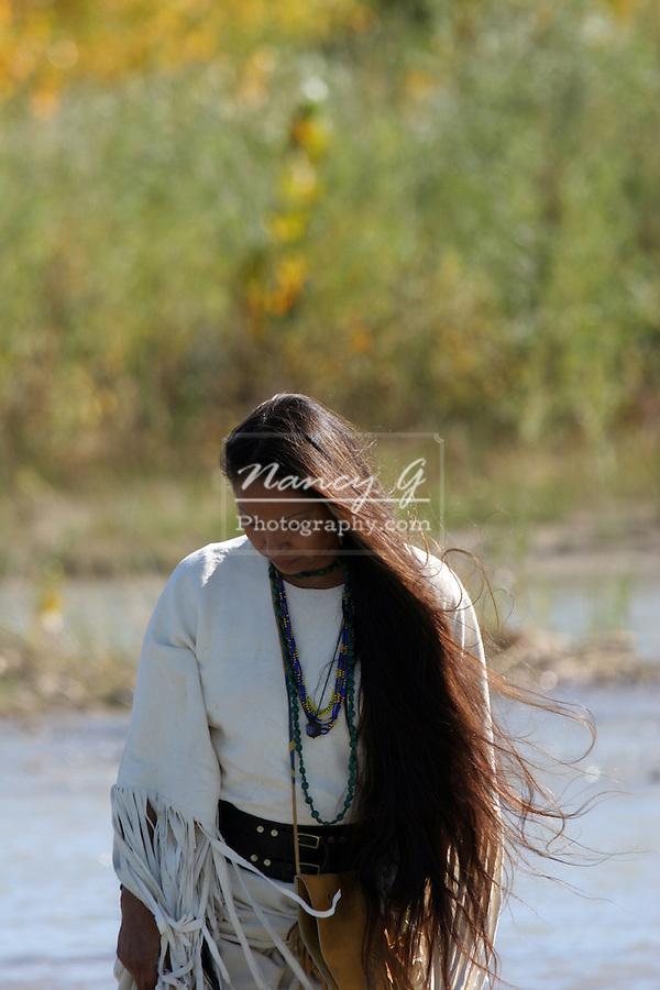 A Native American Indian women walking along the rivers edge in South Dakota
