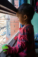 Sujal Tamang (2) looks out the window of his aunt's apartment on the 5th floor in Jorpati, Kathmandu, Nepal on 2 July 2015. Sujal was buried under the rubble of his collapsed house for 36 hours before rescuers found him injured with a broken leg next to his mother who was killed on the spot. Photo by Suzanne Lee for SOS Children's Villages