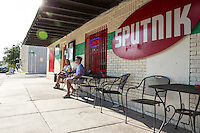 East Austin's East 6th Street is the new and upcoming vibrant section of Austin to hang out as a young attractive business couple enjoys a cold beer.
