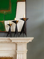 A trio of distinctive candlesticks is displayed on the right-hand side of the mantelpiece in the living room with an artwork by Sandra Blow behind