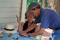 Man showing a female tourist how to roll a cigar, Vinales, Pinar del Rio Province, Cuba.