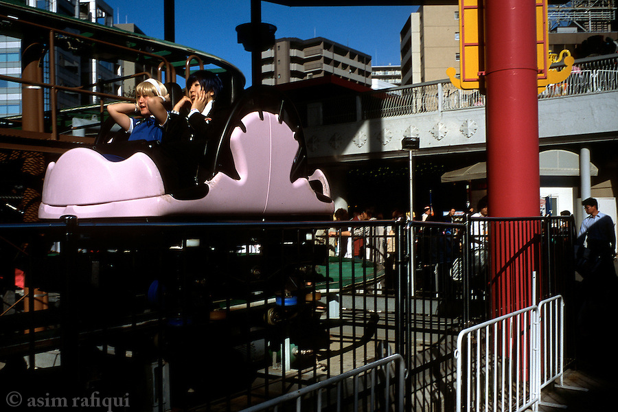 Two girls dressed as their favorite manga characters enjoy a ride at a Tokyo amusement park.
