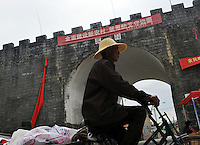 The old city gate at Ruili, China, is draped with a sign that warns against drugs use and trafficking. Chinese-Burmese gangs control drugs that are freely available clubs in the area. The drugs come from Burma....PHOTO BY SINOPIX