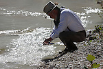 A claim digger panning for gold in a stream in Texas  The light is shinning up from the water in the pan