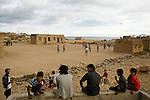 Soccer game played on rock field between buildings, Hawf Protected Area, Yemen