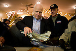 Sen. John McCain (R-AZ) signs a model airplane for retired marine pilot Hoby Harmon, of Bridgewater (right) during a campaign stop in Bridgewater, NH, on Tuesday, Jan. 1, 2008.