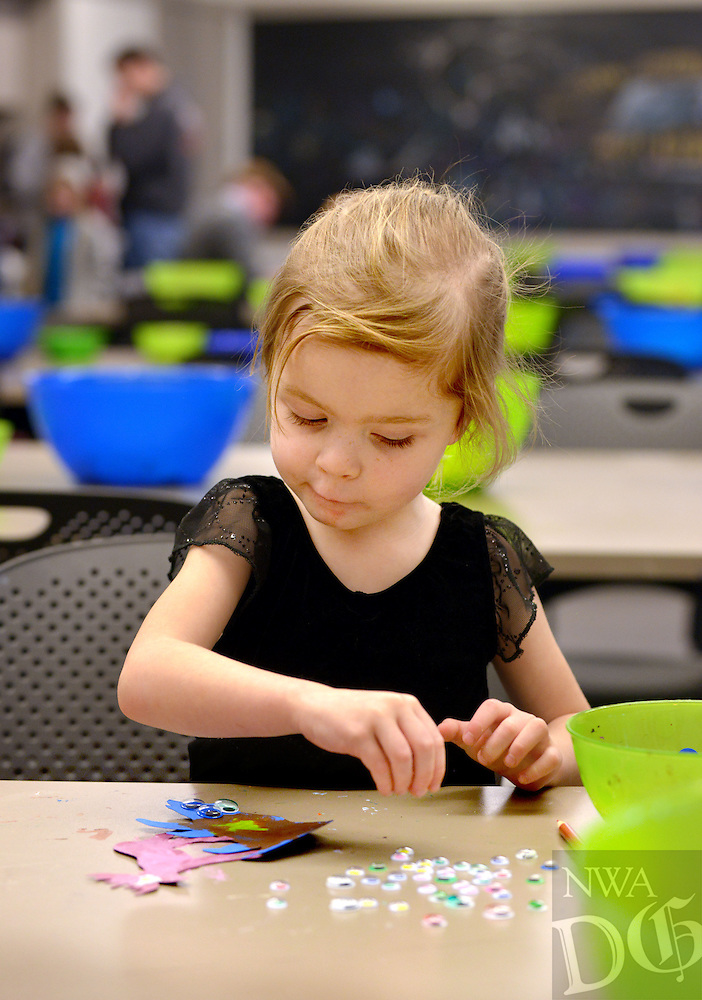 STAFF PHOTO BEN GOFF  @NWABenGoff -- 12/27/14 Tatum Rupp, 3, of Bentonville decorates her animal cutout with colored pencils and googly eyes during the Winter Break Wonders: Winter Animals free drop-in program at Crystal Bridges Museum of American Art in Bentonville on Saturday Dec. 27, 2014.