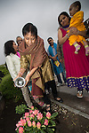 © Joel Goodman . 18 May 2013 . Gita Bhavan Hindu Temple , Withington Road , Whalley Range , Manchester .  Mrs Kusum Vyas PHD waters newly planted plant on the temple grounds in front of the temple . Commemorative service to celebrate the handover of the Green Kumbh Yatra (green journey pot or environmental pilgrimage) at the Gita Bhavan Hindu Temple in Manchester . The pot has travelled to the Maha Kumbh Mela , Kenya , Nepal and the Western Wall in Jerusalem along the way . At every place of rest an environmental action must be taken to reflect the pot's environmental significance . It's due to travel to Leicester and feature in an outdoor procession in London on 24th May 2013 . Photo credit : Joel Goodman