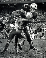 Oakland Raider defensive lineman Ben Davidson slams Miami Dolphin QB Bob Griese to the turf. (copyright 1969 Ron Riesterer)