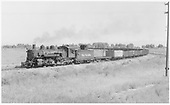 D&amp;RGW #491 with a narrow gauge freight on three-rail track - standard gauge idler, narrow gauge water car and lots of gons.  May be on wye approaching Alamosa yards.<br /> D&amp;RGW  Alamosa, CO  Taken by Richardson, Robert W.