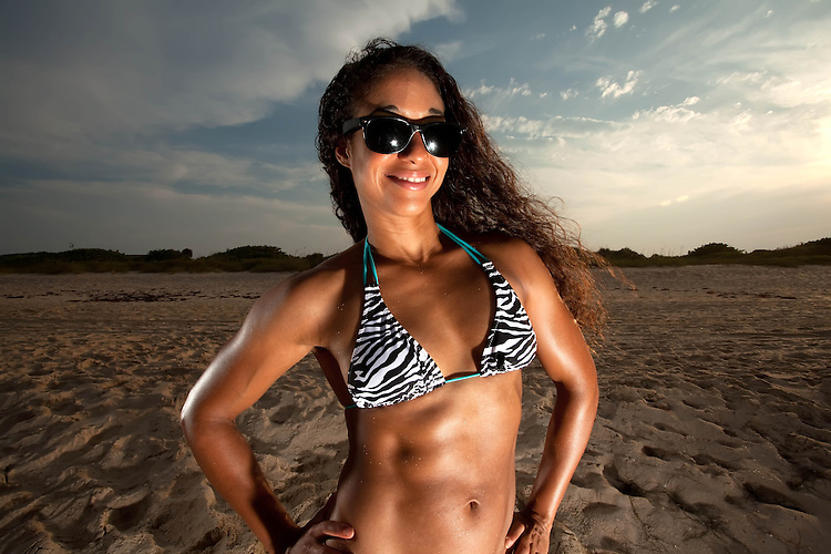 Young Brunette Woman wearing sunglasses at the beach