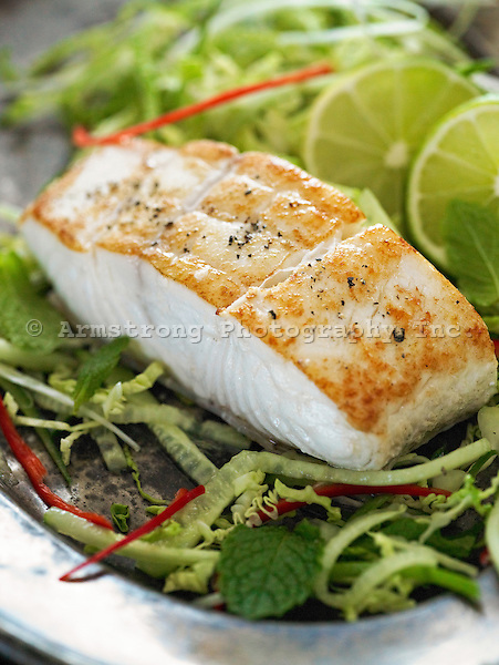 Fresh fillet of seared halibut on bed of fresh greens, cucumbers and mint with fresh slices of lime.