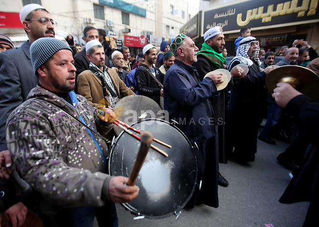 "Palestinians Muslim Sufis play musical instruments as they parade through the streets during a ceremony commemorating the birth of Prophet Mohammed, known in Arabic as ""Mawlid al-Nabawi"", in the West Bank city of Nablus on December 11, 2016. Photo by Nedal Eshtayah"