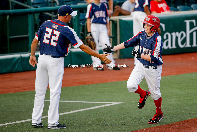 ABERDEEN, MD - AUGUST 02: Cole Dickinson #12 of New Milford (CT) is congratulated by coach Rob Hibbard #22 after hitting a home run against Southeast Denver (CO) in a game between New England and Midwest Plains during the Cal Ripken World Series at The Ripken Experience Powered by Under Armour on August 2, 2016 in Aberdeen, Maryland. (Photo by Ripken Baseball/Eclipse Sportswire/Getty Images)