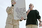 """With the help of cue cards held by an Army soldier, David Letterman delivered his opening monologue written specifically for the troops during """"The Late Show"""" at Camp Taqaddum, Iraq, December 24, 2004. Letterman, along with his musical director Paul Shaffer and stage manager Biff Henderson, brought the popular late night television show to the Marines, sailors and soldiers currently stationed at Camp Taqaddum, Iraq. They were followed with a performance from """"Off the Wall,"""" a southern California band, which added to the holiday festivities. .Mandatory Credit: Luis R. Agostini / USMC via CNP."""