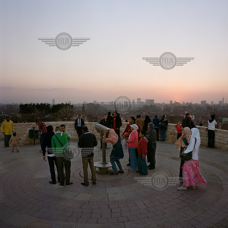 Families and young couples use a telescope to look at the city from the Al Azar Park on the Citadel.