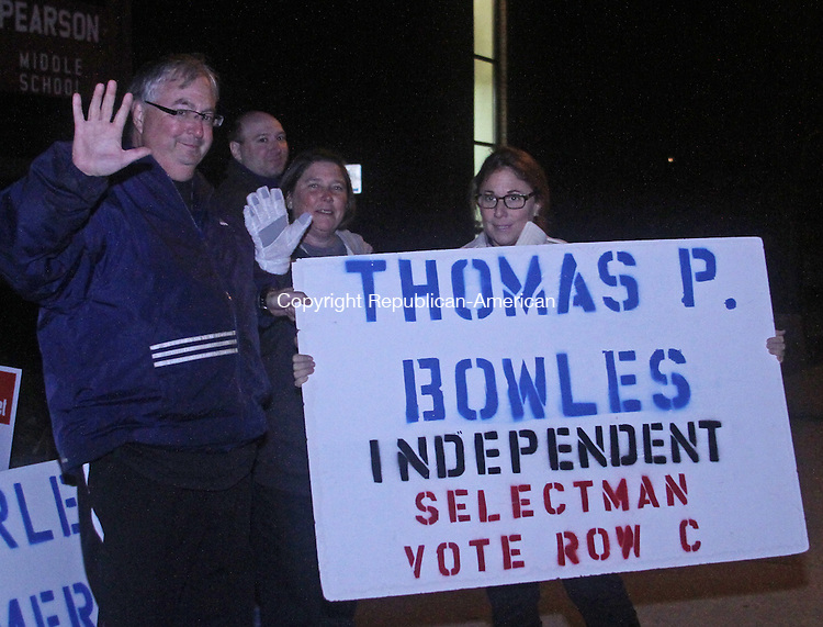 Winsted, CT-110513MK08 Candidate Thomas Bowles waves as his sister Fay Bowles-Higby holds his campaign sign at the entrance to the Pearson Middle School in Winsted to Tuesday night.  There were sixteen candidates running for the Winsted Board of Selectmen.  Poll worker Georgi Andrews said that the turn out by the voters had been steady throughout the day . Michael Kabelka / Republican-American.
