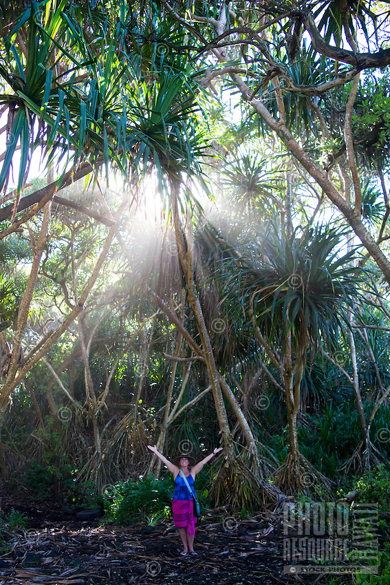Sun rays filter through the trees over a smiling woman with outstretched arms in Kapoho, Puna district, Hawai'i Island.