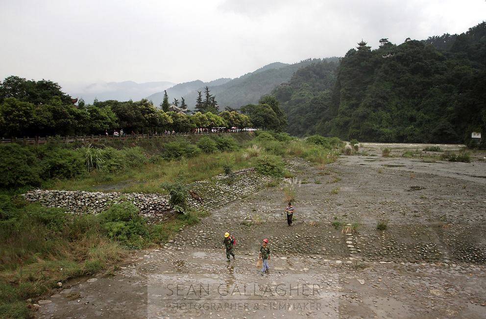 "Workers walk up one of the channels that make up the Dujiangyan Irrigation System. The system is regarded as an ""ancient Chinese engineering marvel."" By naturally channeling water from the Min River during times of flood, the irrigation system served to protect the local area from flooding and provide water to the Chengdu basin. Sichuan Province. 2010"