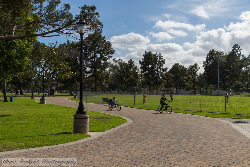 A man and a boy ride bikes along the paver pathway at South Gate Park in front of a famil of three tossing balls around on the baseball field.