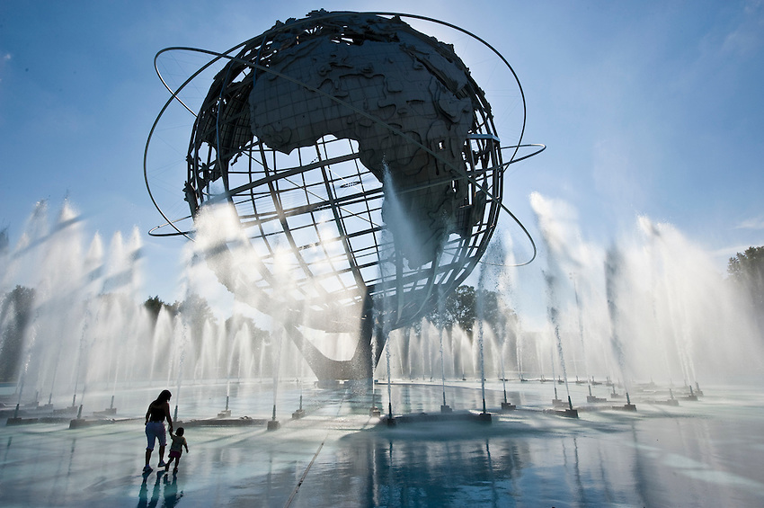 A mother and small child enjoying the spray from the water fountains at the Unisphere, also known as the Globitron, in Flushing Meadows Park, in the borough of Queens, New York City on a bright sunny afternoon. Originally built in April 1964 for the New York World's Fair, is currently the site of the U.S. Open tennis championship.