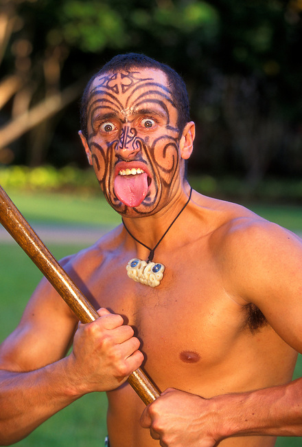Maori warrior with tongue out (model released) at the Polynesian Cultural Center, Laie, Oahu Island, Hawaii, United States..