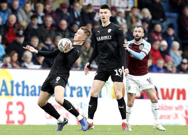 Barnsley's Cauley Woodrow controls as Kieffer Moore and Burnley's Steven Defour look on<br /> <br /> Photographer Rich Linley/CameraSport<br /> <br /> Emirates FA Cup Third Round - Burnley v Barnsley - Saturday 5th January 2019 - Turf Moor - Burnley<br />  <br /> World Copyright © 2019 CameraSport. All rights reserved. 43 Linden Ave. Countesthorpe. Leicester. England. LE8 5PG - Tel: +44 (0) 116 277 4147 - admin@camerasport.com - www.camerasport.com